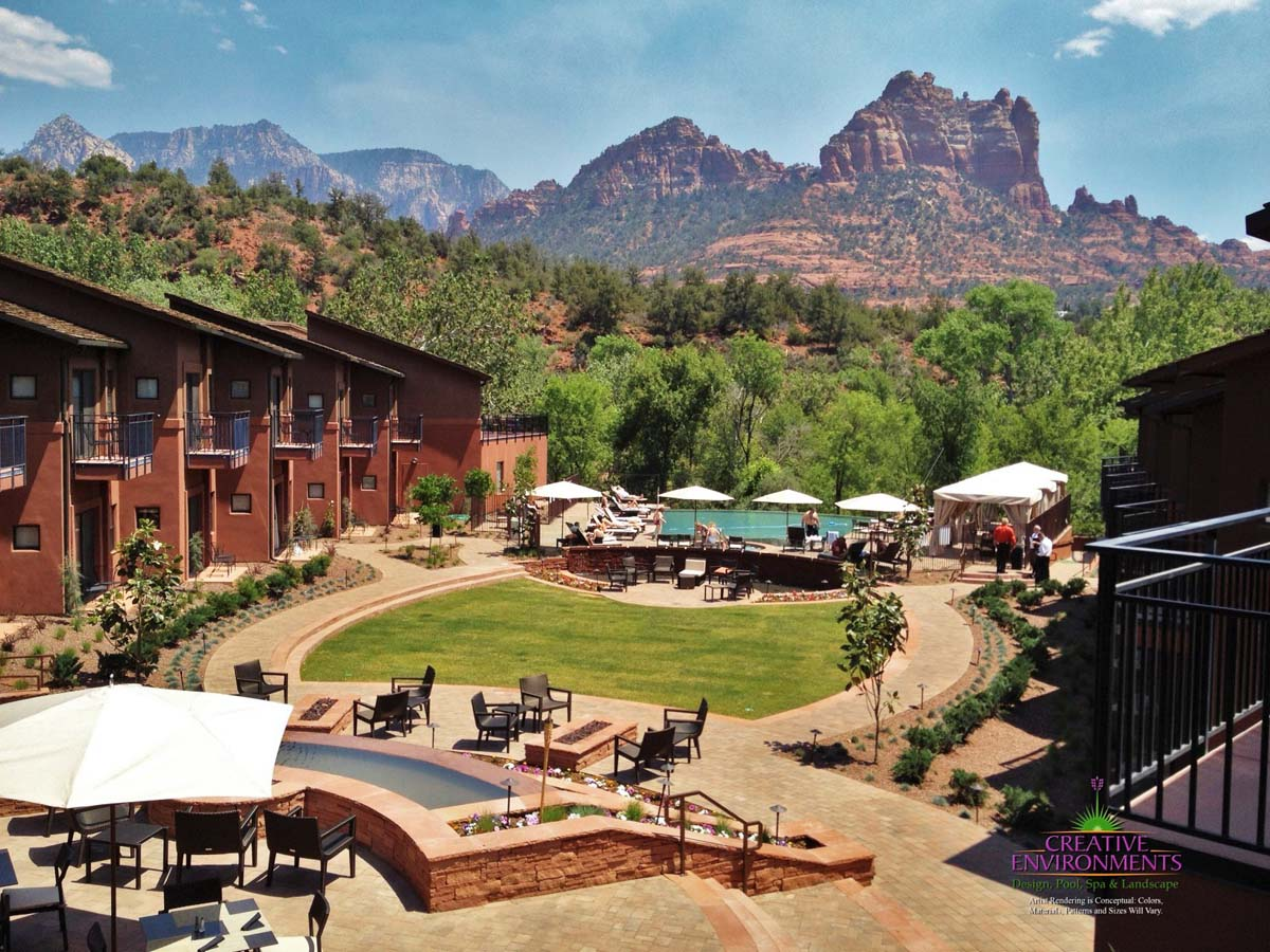 Large courtyard of hotel in Sedona with grass area, large water feature, desert landscape, and pool
