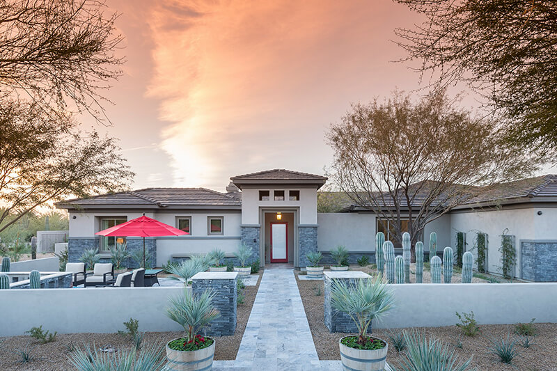 Desert landscape design with fire feature in front walkway to home