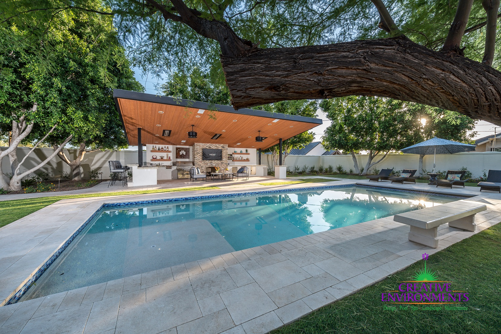 Large custom pool with covered patio space for an outdoor kitchen