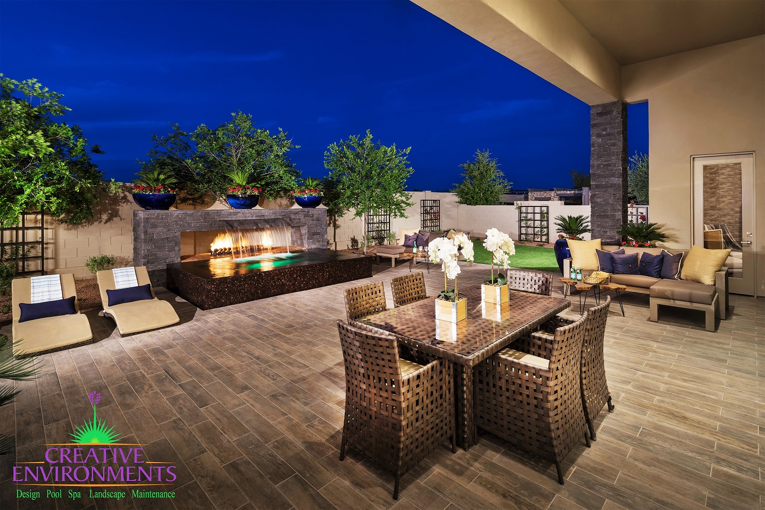 Extended patio area with outdoor dining and zero edge pool with waterfall