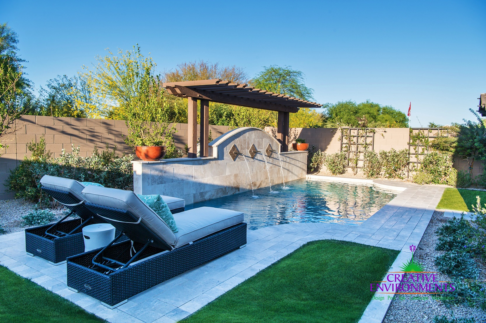Small custom pool with water feature and wood pergola