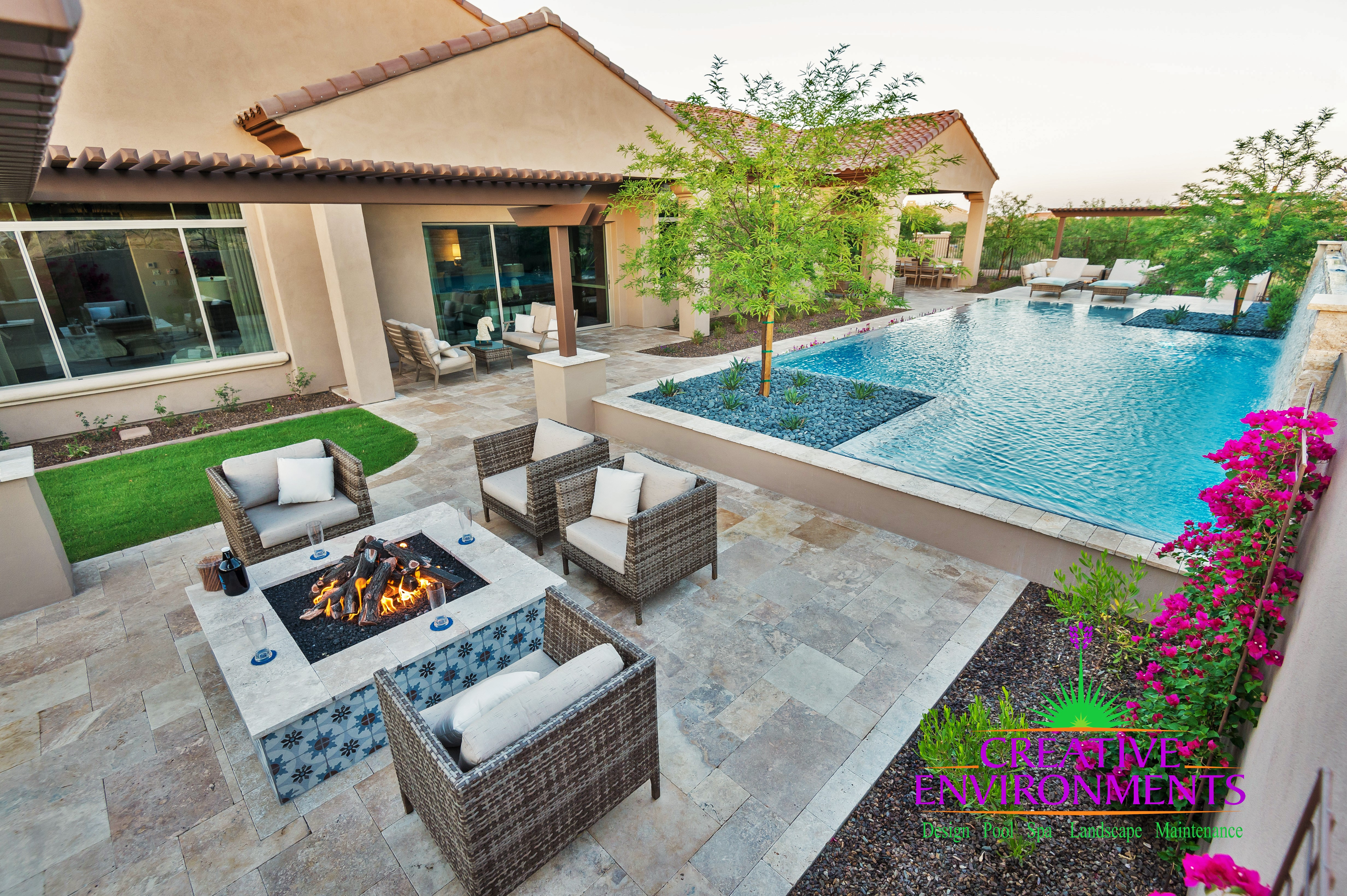 Infinity pool with a hot tub near a custom fire feature